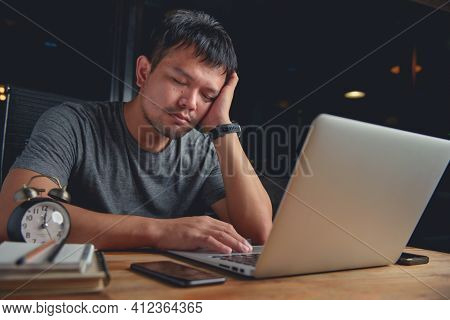 Asian Man Worked Hard Until Late At Night And Was So Tired That He Was Asleep At The Desk. Concept O
