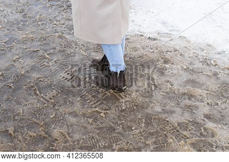 A Woman Standing In The Melted Snow, Cropped. Thaw, Slush, Dampness