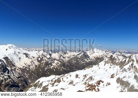 Mountain Snow Panorama On Main Chain Of The Alps Seen From Summit Sexegertenspitze And Blue Sky In T