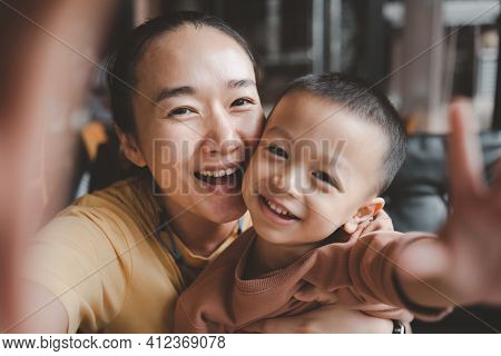 Asian Beautiful Mother And Child Happily Beautiful Young Mom And Cute Little Boy Are Sitting Togethe
