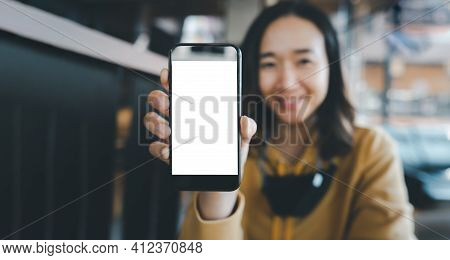 Happy Woman Showing Blank Smartphone Screen In Cafe, Mockup Mobile Phone With Blank White Screen.