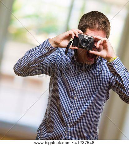 Handsome Man Looking Through A Vintage Camera, indoor poster