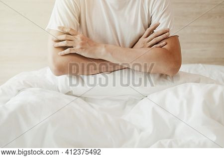 A Man Sitting On The Bed And Crossed Arms On White Bed In Bedroom With And Sunlight.