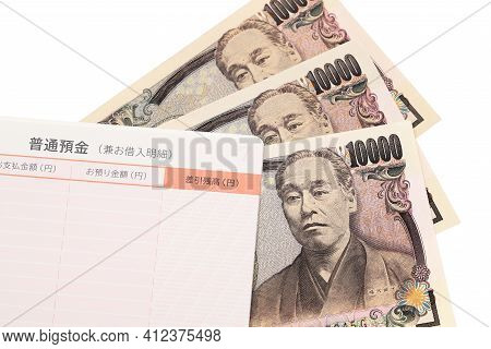 Ten Thousand Japanese Yen With Passbook Isolated On White Background. Translation: Ordinary Bank Acc