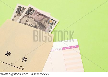 Japanese Money And Passbook With Salary Bag Isolated On Table. Translation: Salary, Year, Month, Day