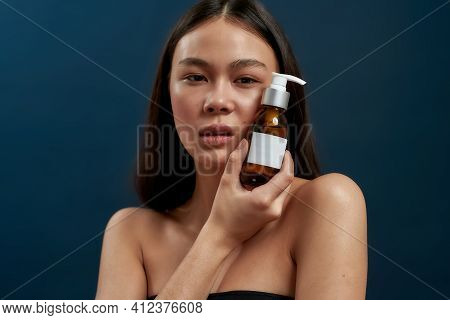 Cute Asian Girl Looking At The Camera While Holding Skin Care Products Near Her. Healthy Skin Care C