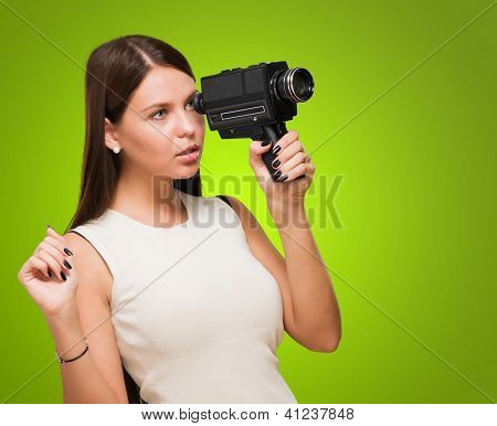 Portrait Of A Young Woman Holding Video Camera against a green background