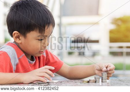 Portrait Of Happy Asian Child Boy Counting The Coins. Childhood Put The Money On The Table. Kid Savi