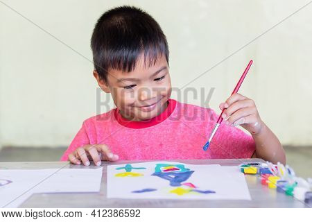 Portrait Image Of 5-6 Yeas Old Child Boy. Asian Student Drawing And Painting Colours On The Paper In