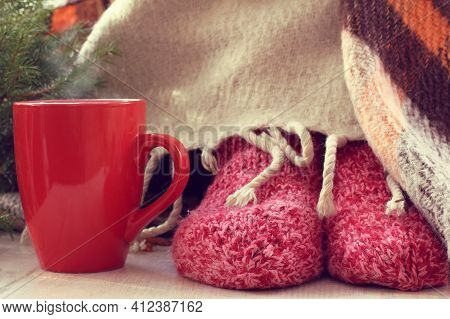 Legs In Knitted Socks And A Plaid, Next To A Red Mug With A Hot Drink And A Christmas Tree. Warming
