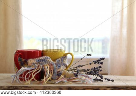 Pair Of Mugs In A Knitted Scarf On A Table With A Bouquet Of Lavender On A Window Background. Romant