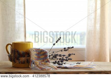 Yellow Mug In A Knitted Scarf And A Bouquet Of Flowers On A Window Background. Cozy Coffee With Lave