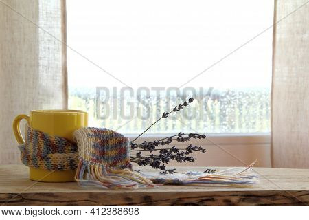 Yellow Mug In A Knitted Scarf And A Bouquet Of Lavender On The Background Of A Window After Rain. Wa