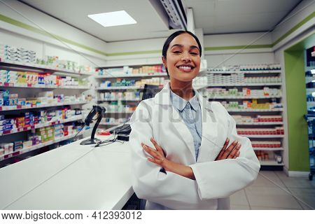 Proud Young Female With Folded Hands In Labcoat Standing In Chemist Near Counter