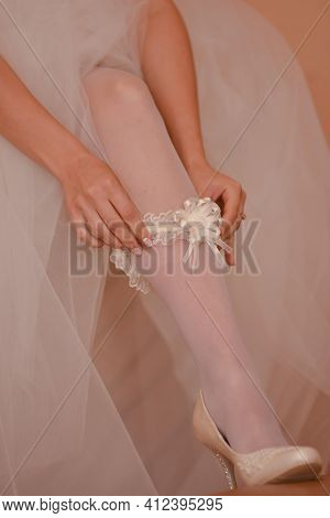 The Bride Puts A Garter On Her Leg.