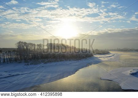 Picturesque Landscape With Snowy Forest On The Bank Of River With Ice In Winter.
