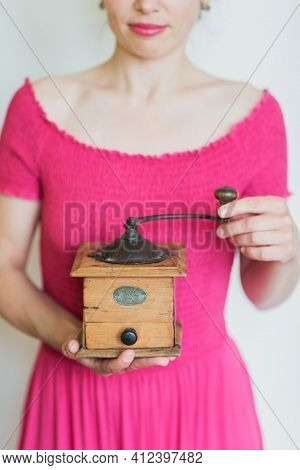 Beautiful Smiling Woman In Pink Dress Holds A Manual Wooden Coffee Grinder In Her Hands.