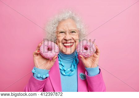 Positive Beautiful Wrinkled Elederly European Woman Holds Two Delicious Glazed Doughnuts Smiles Broa