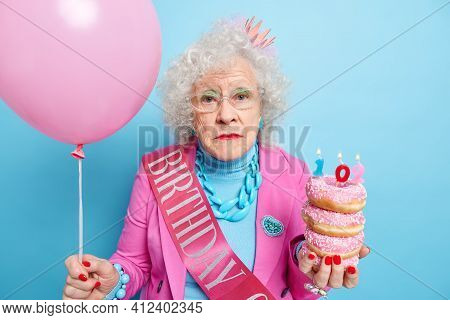 Portrait Of Serious Beautiful Mature Lady Looks At Camera With Melancholy Expression Holds Pile Of G