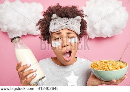 Early Awakening And Morning Time Concept. Sleepy Dark Skinned Woman Yawns Has Lack Of Sleep Has Brea