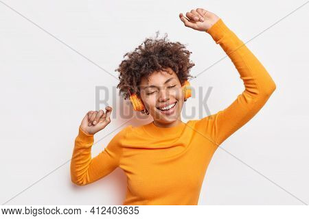 Happy Young Afro American Woman Carried Away With Music Dances Carefree With Arms Raised Keeps Eyes