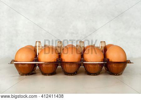 Ten Brown Eggs In A Plastic Wrap.