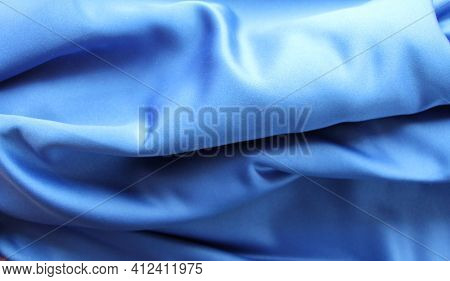Delicate Shiny Fabric Of Blue Silk Laid Out In Large Waves, The Effect Of Smooth Movement Of The Mat