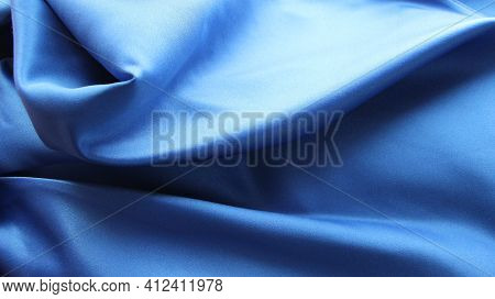 Blue Luxurious Shiny Material Rolled Up In Neat Graceful Folds, Flowing Silk With A Metallic Sheen,