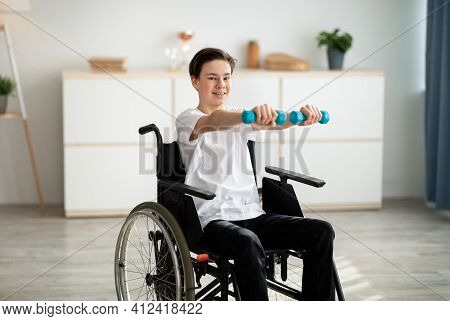 Physical Rehabilitation For Disabled People. Handicapped Teenager In Wheelchair Making Exerises With
