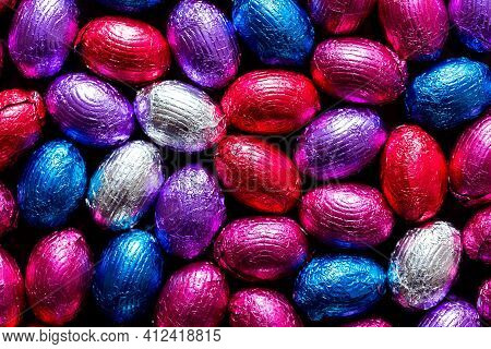 A Portrait Of A Lot Of Delicious Chocolate Easter Eggs Wrapped In Colorful Tin Foil. There Are Red,