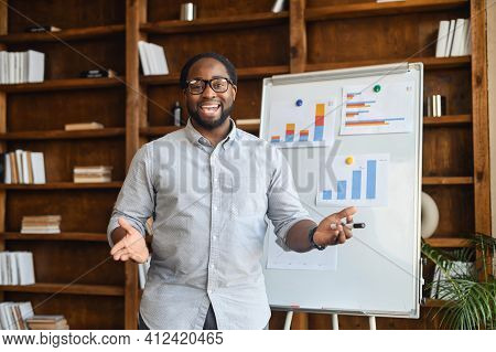 African American School Teacher In Glasses Standing Next To Whiteboard With Bar Charts, Explaining M