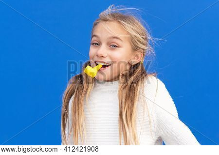 Studio Portrait Of A Happy, Smiling Young Girl Celebrating Birthday Party, Holding Party Blower In M