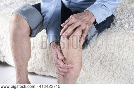 Joint Knee Disease, Bursitis, Arthritis Or Arthrosis. Cropped Shot Of Elderly Man Sitting On Sofa An