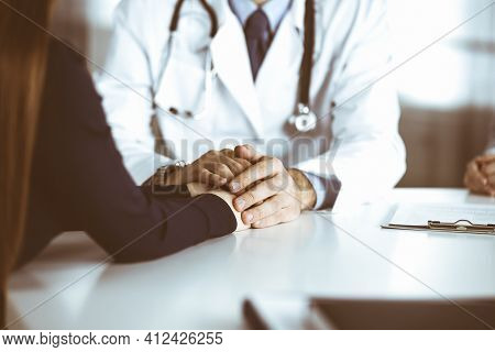 Unknown Man-doctor Reassuring His Female Patient, Close-up. Two Physicians Consulting And Giving Som