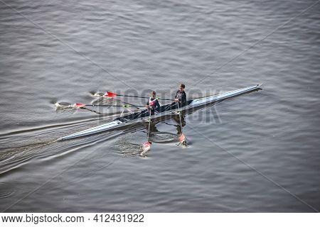 Prague, Czech Republic - February 24, 2021. Two Young Active People Rowing In Moldau River