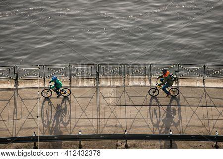 Prague, Czech Republic - February 24, 2021. Cyclist Riding On Vltava Riverbank In Shadow Of The Sun