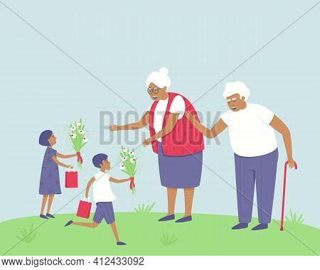 A Girl And A Boy Give Flowers And Gifts To Their Grandparents. Holiday. The Children Are Glad They S