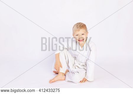 Judo And Sports Concept, Blond Boy Sitting In Kimono On White Background, Place For Text