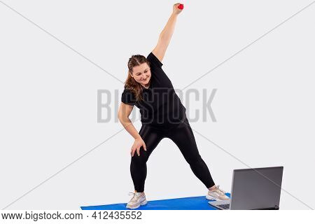 Young Plus Size Woman Sitting On Floor Using Laptop With The Trainer In Online Training, The Athlete