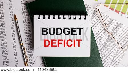 On The Desktop Are Reports, Glasses, A Pen, A Green Diary And A White Notebook With The Words Budget