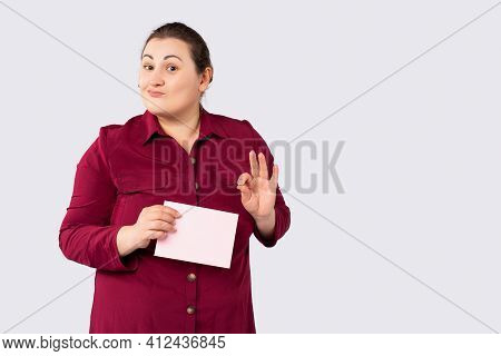 Smiling Overweight Businesswoman Holding Blank Parcel Over Grey Background, Showing Approving Ok Ges