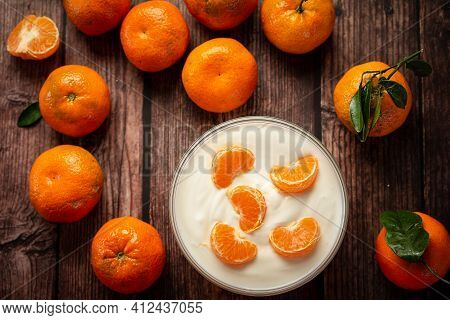 A Bowl Of Yogurt With Ripe Clementines And Tangerines On A Wooden Table.