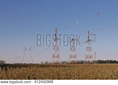 Colored Ball For Air Traffic Hangs From A High-voltage Cable. High Voltage Power Line Towers With Ba