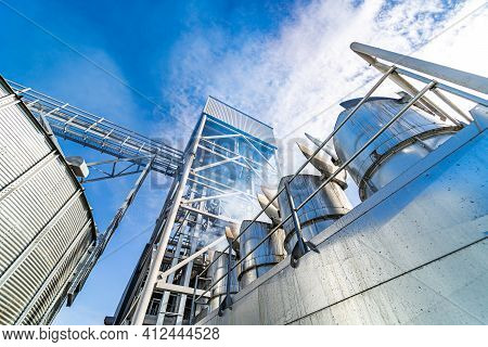 View From Below On Steel Grain Elevators. Industrial Agriculture Elevators With Harvested Grain. Mod