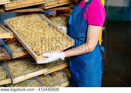 Pasta Factory. Production Of Pasta. Krafted Macaroni. Female Worker With Wooden Box With Pasta. Sele