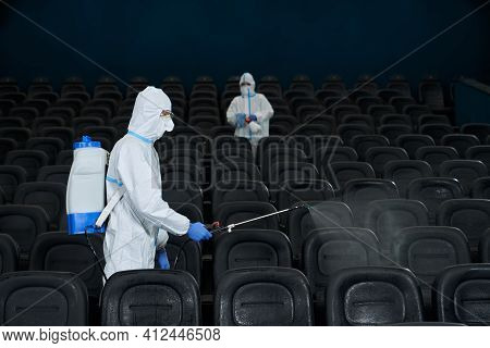 Workers In Protective Anti-virus Clothes Cleaning Cinema Hall With Special Disinfectants. Concept Of