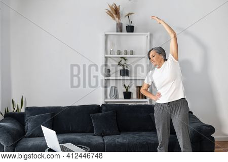 Active And Sporty Senior Female Warming Out Before Workout At Home, An Older Woman Stretching Arms I
