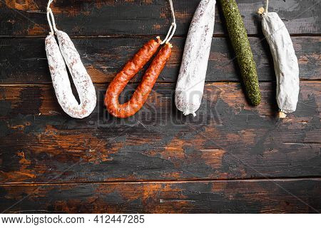 Spanish Salami, Fuet And Chorizo Sausages On Wooden Surface With Space For Text.