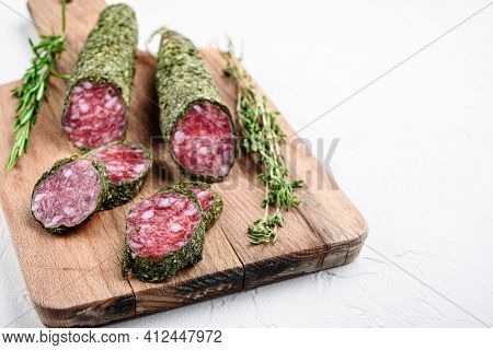 Sliced Cuts Of Fuet Salami Sausage On White Surface With Copy Space.