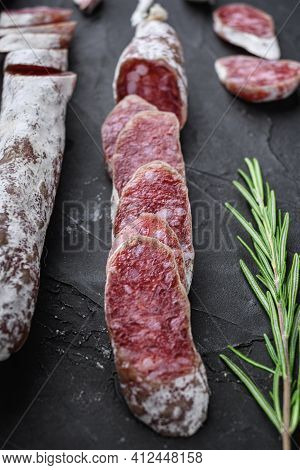 Dry Cured Fuet Salami Sausage Slices  On Balck Background.